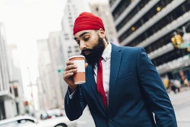 Indian businessman walking in Manhattan, drinking coffee - GIOF01551