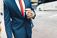 Businessman walking in the city, holding cup of coffee - GIOF01557