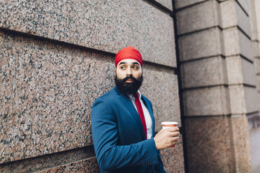 Indian businessman in Manhattan leaning against wall, drinking coffee - GIOF01560