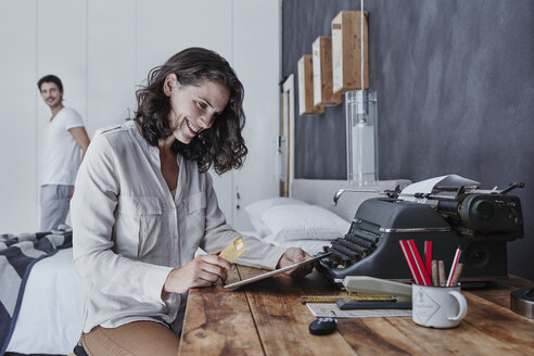 Smiling woman shopping online in bedroom with husband in background - RORF00305