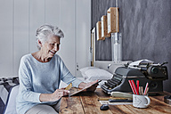 Smiling senior woman shopping online in bedroom - RORF00308