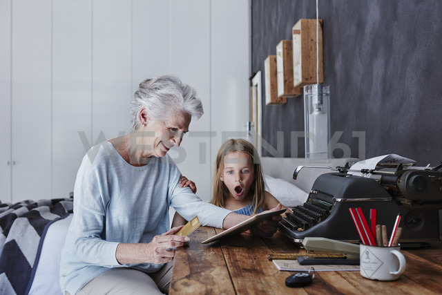 Grandmother and amazed granddaughter shopping online at home - RORF00314 - Roger Richter/Westend61