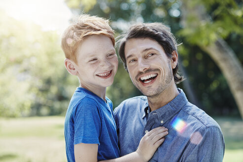 Portrait of happy father with son in garden - RORF00320
