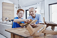 Grandfather and grandson building up model airplanes - RORF00329