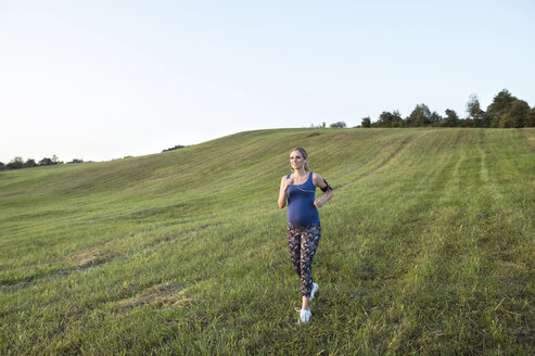 Pregnant woman jogging in field - HAPF01006