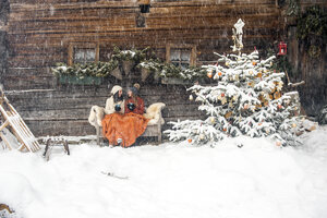 Friends sitting on bench by Christmas tree in front of mountain hut - HHF05432