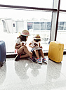 Two little girls waiting at airport, playing with digital tablet - MGOF02517