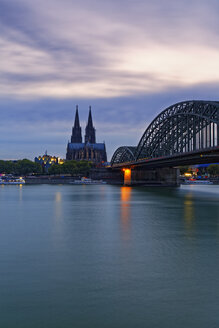 Germany, Cologne, view to Cologne Cathedral with Hohenzollern Bridge in the foreground at evening twilight - GFF00814