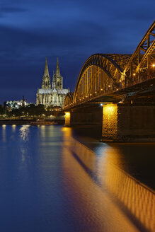 Germany, Cologne, lighted Cologne Cathedral and Hohenzollern Bridge - GFF00817