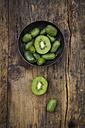 Bowl of sliced and whole hardy kiwis and sliced kiwi on dark wood - LVF05454