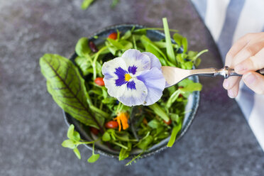 Girl's hand holding fork with pansy in front of bowl with wild-herb salad - SARF03006