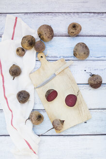 Sliced and whole beetroot and pocket knife on wooden board - LVF05476