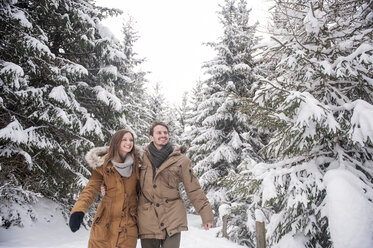 Happy couple walking in winter forest - HHF05443
