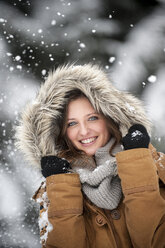 Young woman wearing fur hood in snow fall, portrait - HHF05446