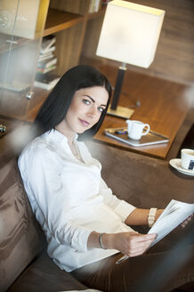 Reading woman sitting in hotel lounge, drinking coffee - HHF05449