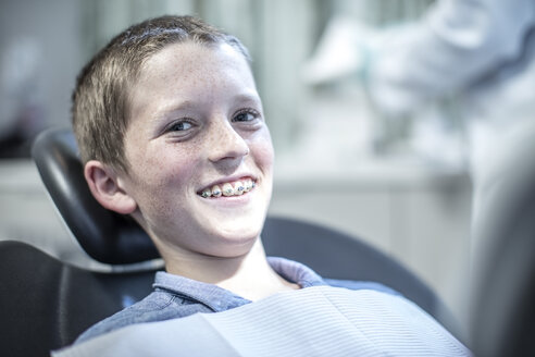 Smiling boy with braces in dental surgery - ZEF10631