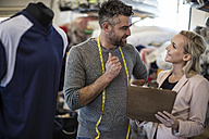 Tailor talking to woman with clipboard in workshop - ZEF10661