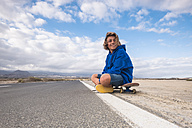 Spain, Tenerife, smiling boy sitting on his skateboard at roadside - SIPF00944
