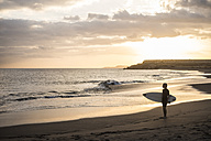 Spain, Tenerife, boy carrying surfboard on the beach at sunset - SIPF00953