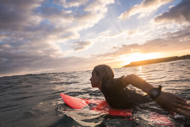 Spain, Tenerife, boy surfing in the sea at sunset - SIPF00965