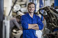 Confident car mechanic in repair garage - ZEF10704