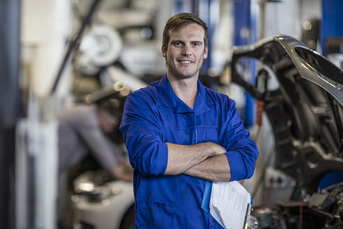 Confident car mechanic in repair garage - ZEF10704