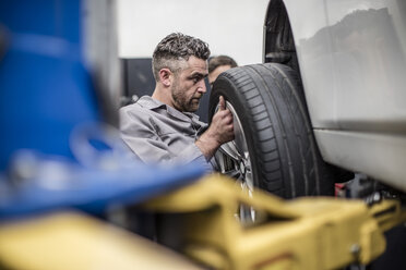 Car mechanic in a workshop changing tire - ZEF10716