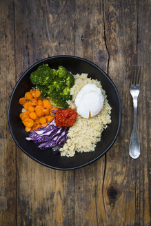 Lunch bowl of quinoa, red cabbage, carrots, roasted chickpeas, broccoli, poached egg and ajvar - LVF05479