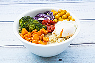 Lunch bowl of quinoa, red cabbage, carrots, roasted chickpeas, broccoli, poached egg and ajvar - LVF05485