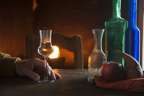 Hand with shot glass and bottles in front of open fire - HHF05453
