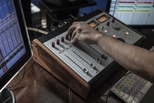 Close-up of audio engineer operating mixer in recording studio - ZEF10753