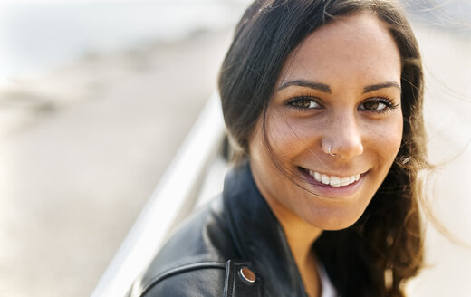 Portrait of smiling young woman with freckles and nose piercing - MGOF02523