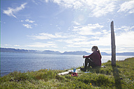 Iceland, hiker resting on a meadow looking at view - RBF05220