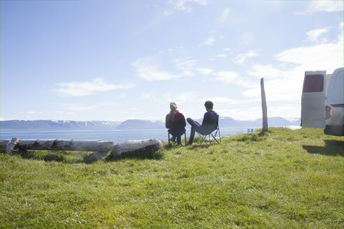 Iceland, back view of couple sitting on camping chairs looking at view - RBF05223