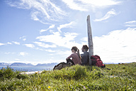 Iceland, hiking couple resting on a meadow looking at view - RBF05226