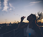 Young woman blowing soap bubbles on roof terrace in the evening twilight - AIF00408