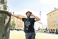 Germany, Berlin, smiling man on the phone with television tower in the background - TAMF00694