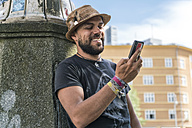 Portrait of smiling man looking at his smartphone - TAMF00697