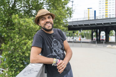 Portrait of smiling man wearing hat leaning on railing - TAMF00700