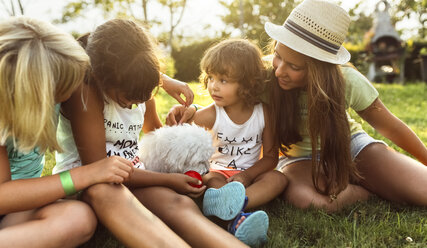 Four girls playing with a puppy on a meadow - MGOF02531