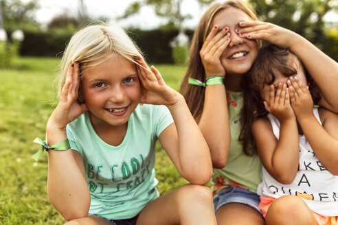Three girls having fun together on a meadow - MGOF02543