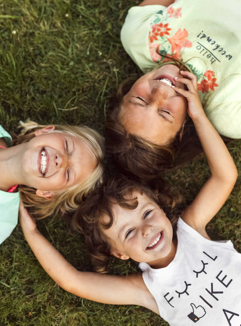 Three smiling girls lying head to head  on a meadow - MGOF02546 - Marco Govel/Westend61