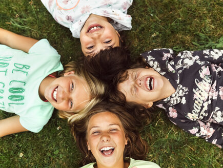 Four laughing girls lying head to head  on a meadow - MGOF02549