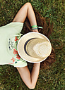 Girl with straw hat on her face lying on a meadow - MGOF02555