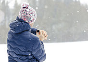 Back view of sportive man checking his smartwatch in winter - MMAF00005