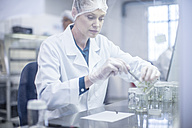 Woman wearing protective clothing working in lab - ZEF10840