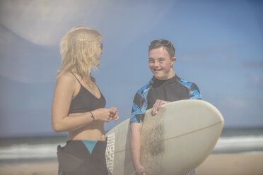 Teenage boy with down syndrome and woman with surfboard on beach - ZEF10865