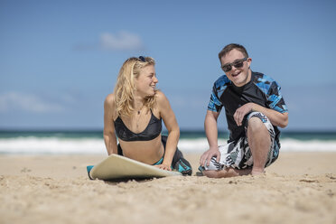 Teenage boy with down syndrome having surf lessons on beach - ZEF10868