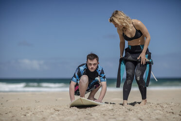 Teenage boy with down syndrome having surf lessons on beach - ZEF10871