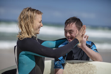 Happy teenage boy with down syndrome and woman with surfboard on beach - ZEF10874